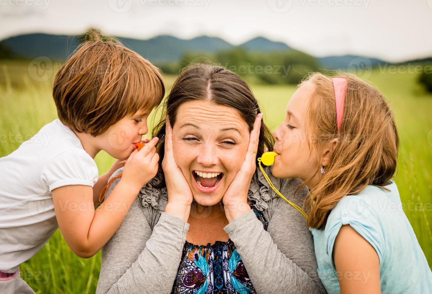 Children blowing whistle to mother's ears photo