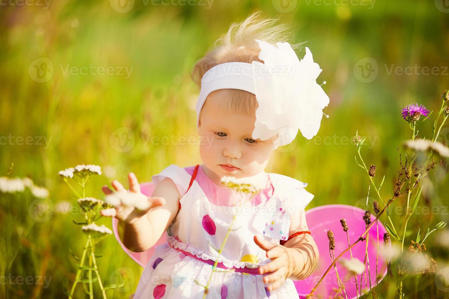 beautiful carefree girl playing outdoors in field with high gree photo