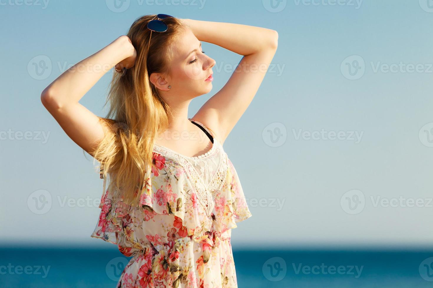 Summer vacation. Girl standing alone on the beach. photo