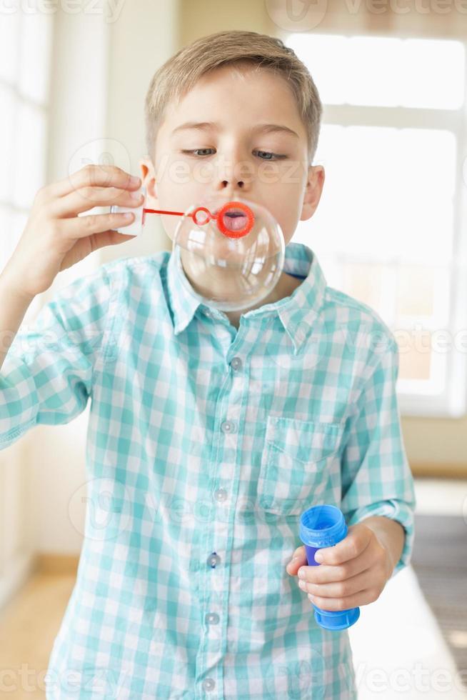 Chico lindo jugando con la varita de burbujas en casa foto