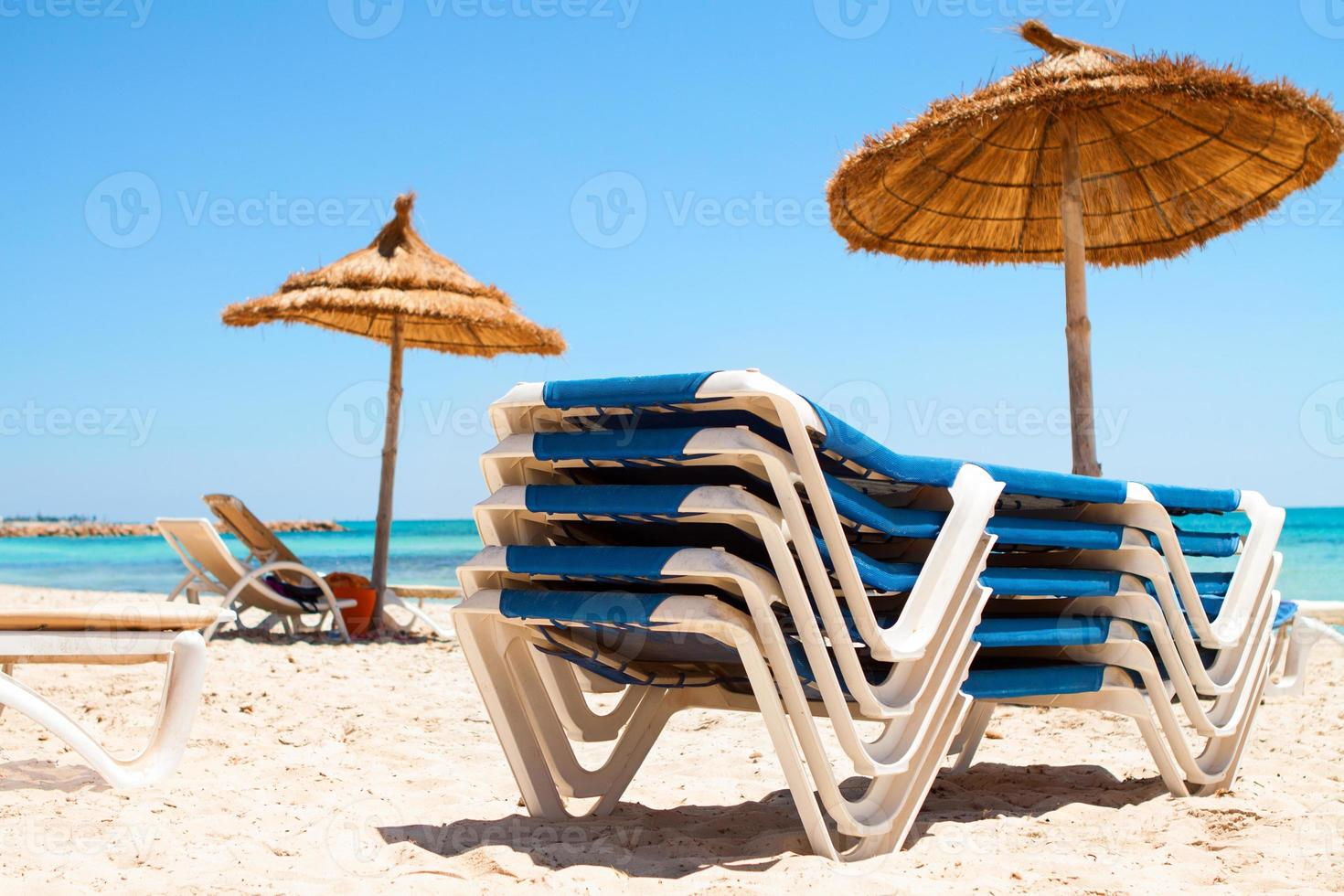 Deck chairs and parasol on the beach photo