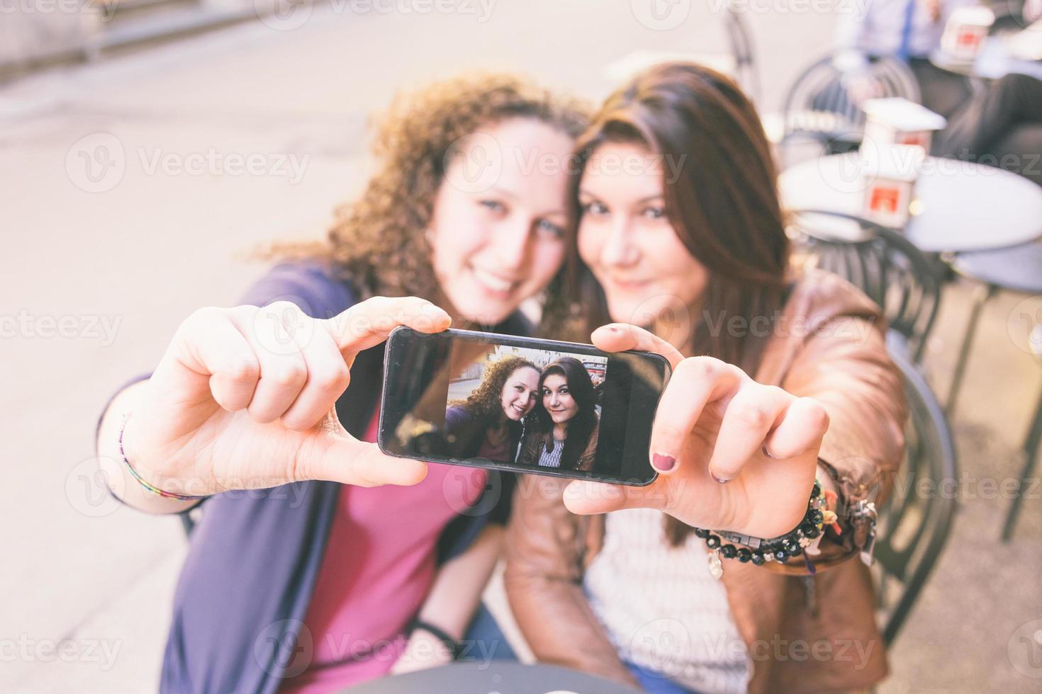 chicas tomando selfie sentado en el bar foto