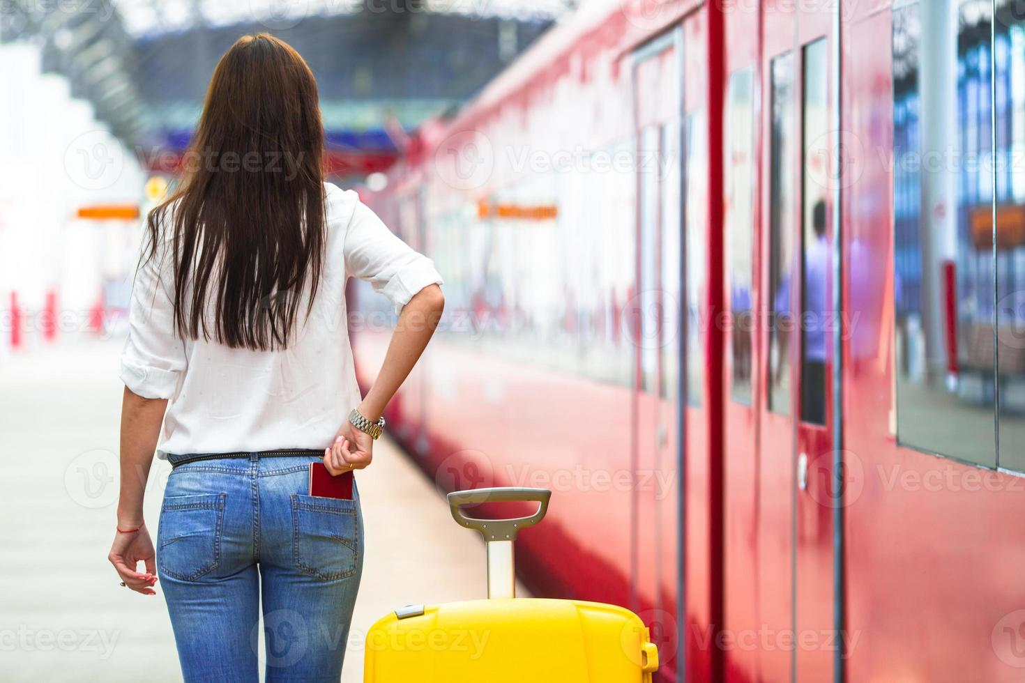 Young caucasian girl with luggage at station traveling by train photo