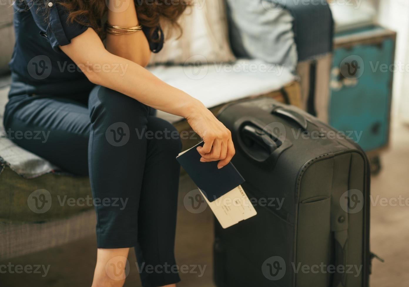 closeup on young woman with passport, ticket and luggage photo