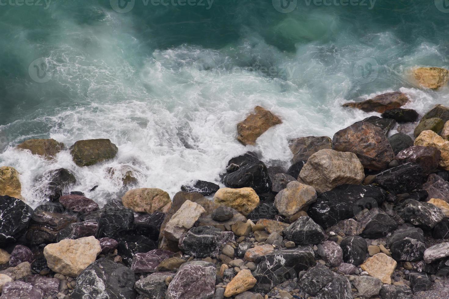 ondas quebrando em uma praia rochosa colorida em vernazza, cinque terre foto