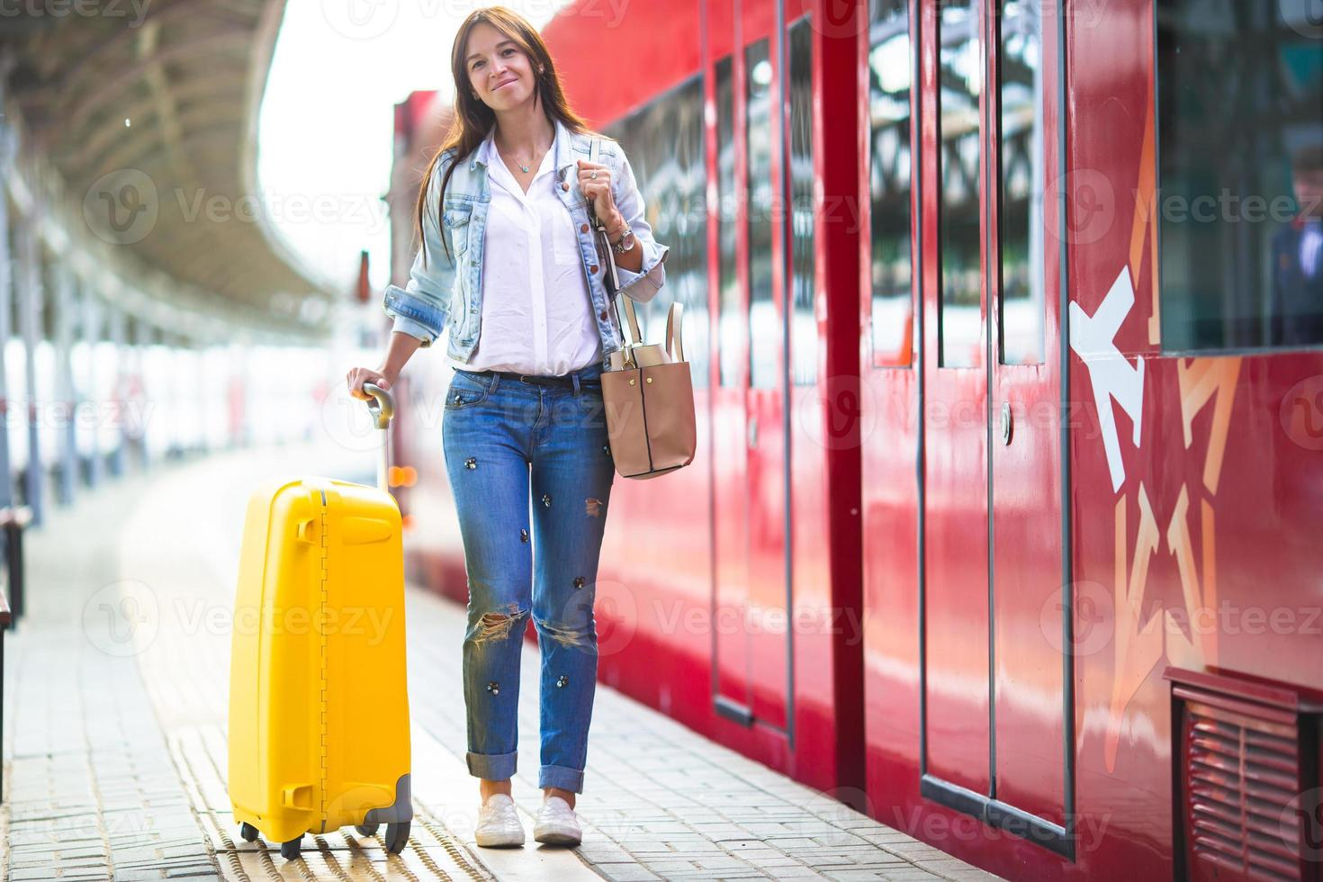 Young woman with luggage at train station waiting for train photo