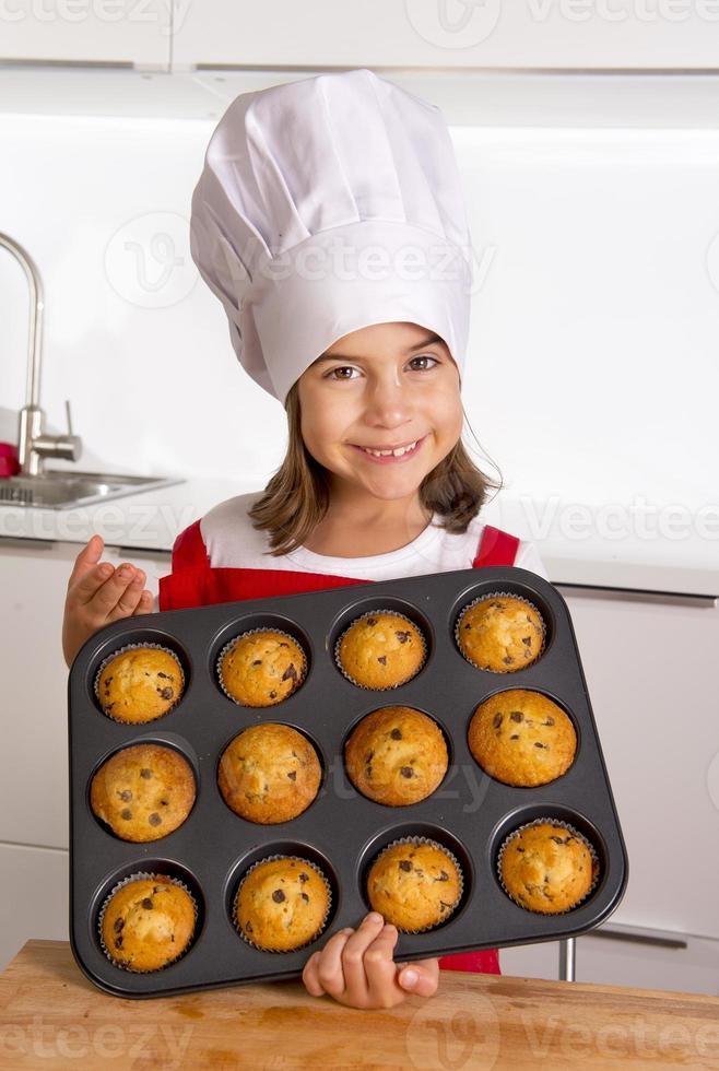 criança orgulhosa e feliz apresentando bolos de muffin e aprendendo a cozinhar foto