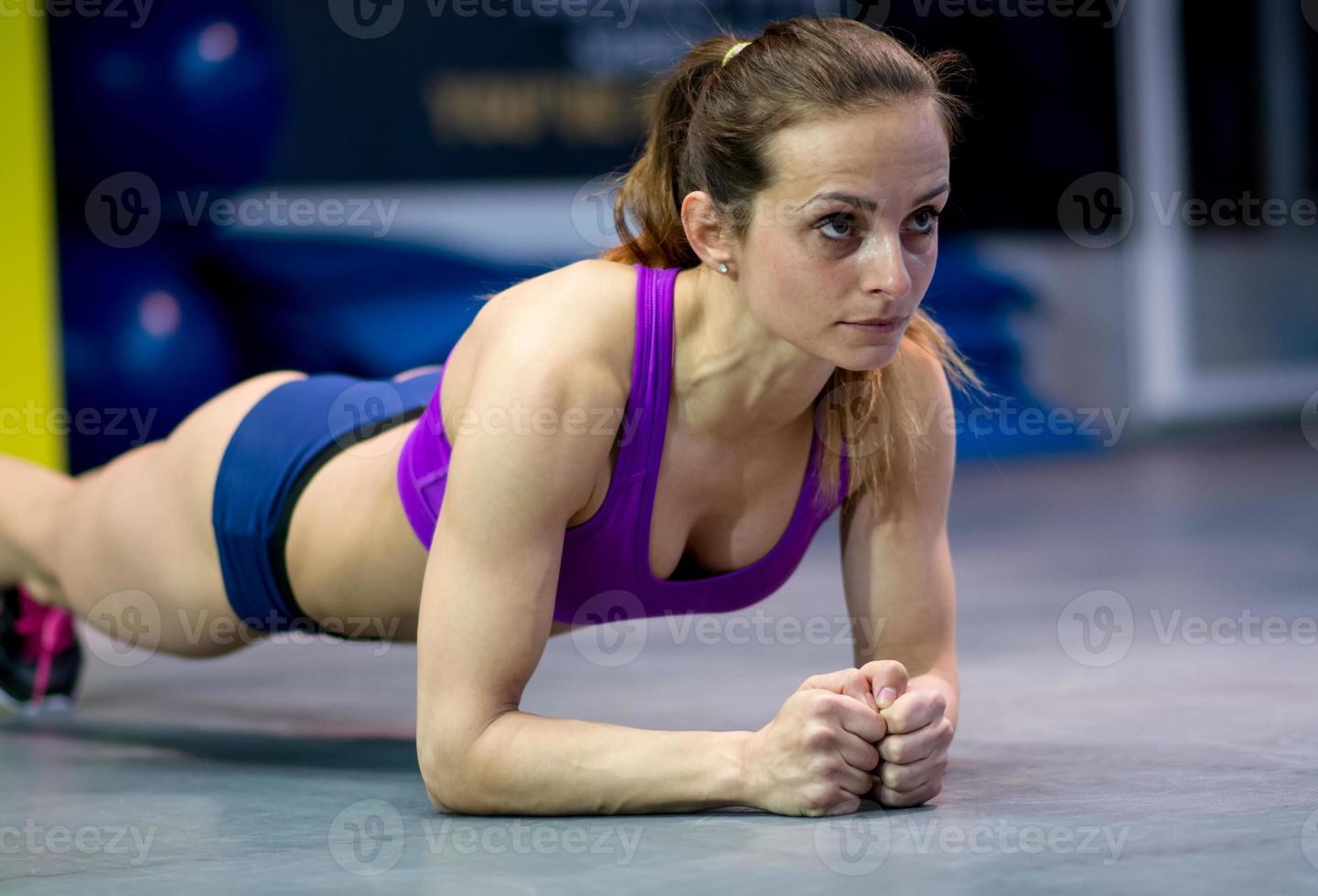 young woman stretching in the gym photo