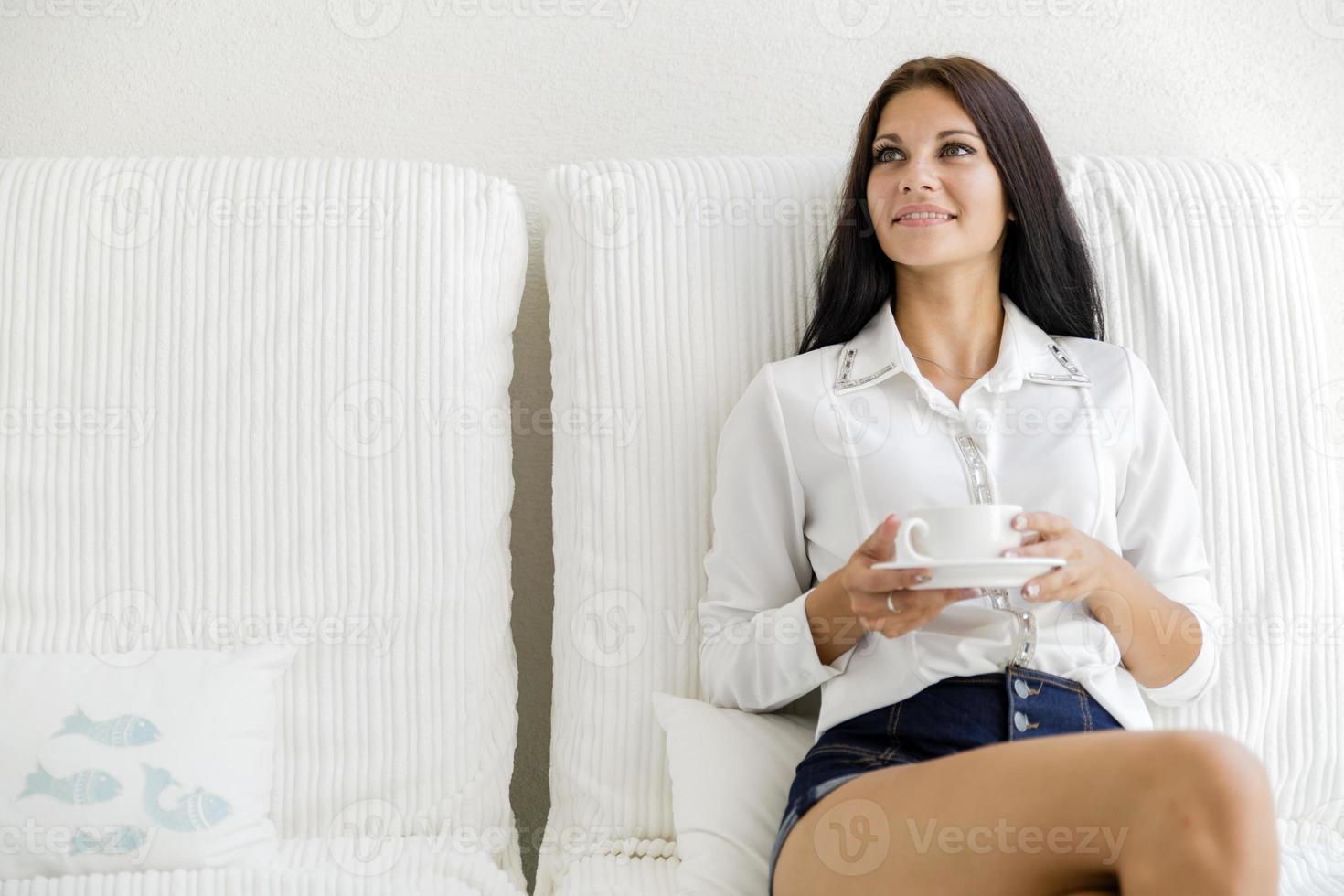 linda mulher tomando café em uma xícara branca foto