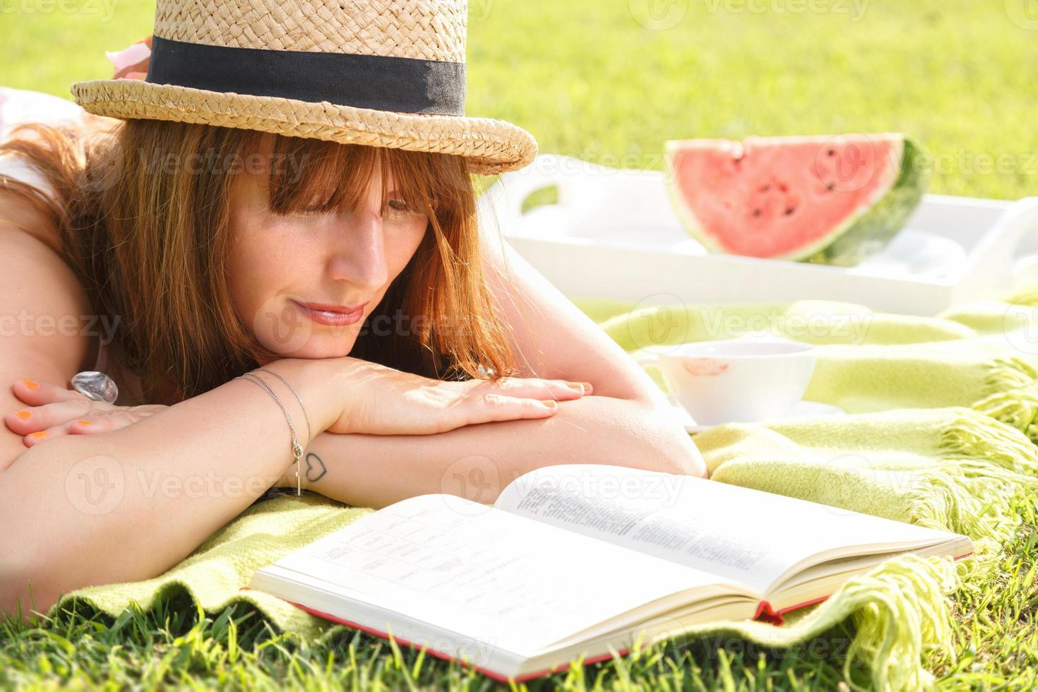 Atractive young female reading book in the park photo