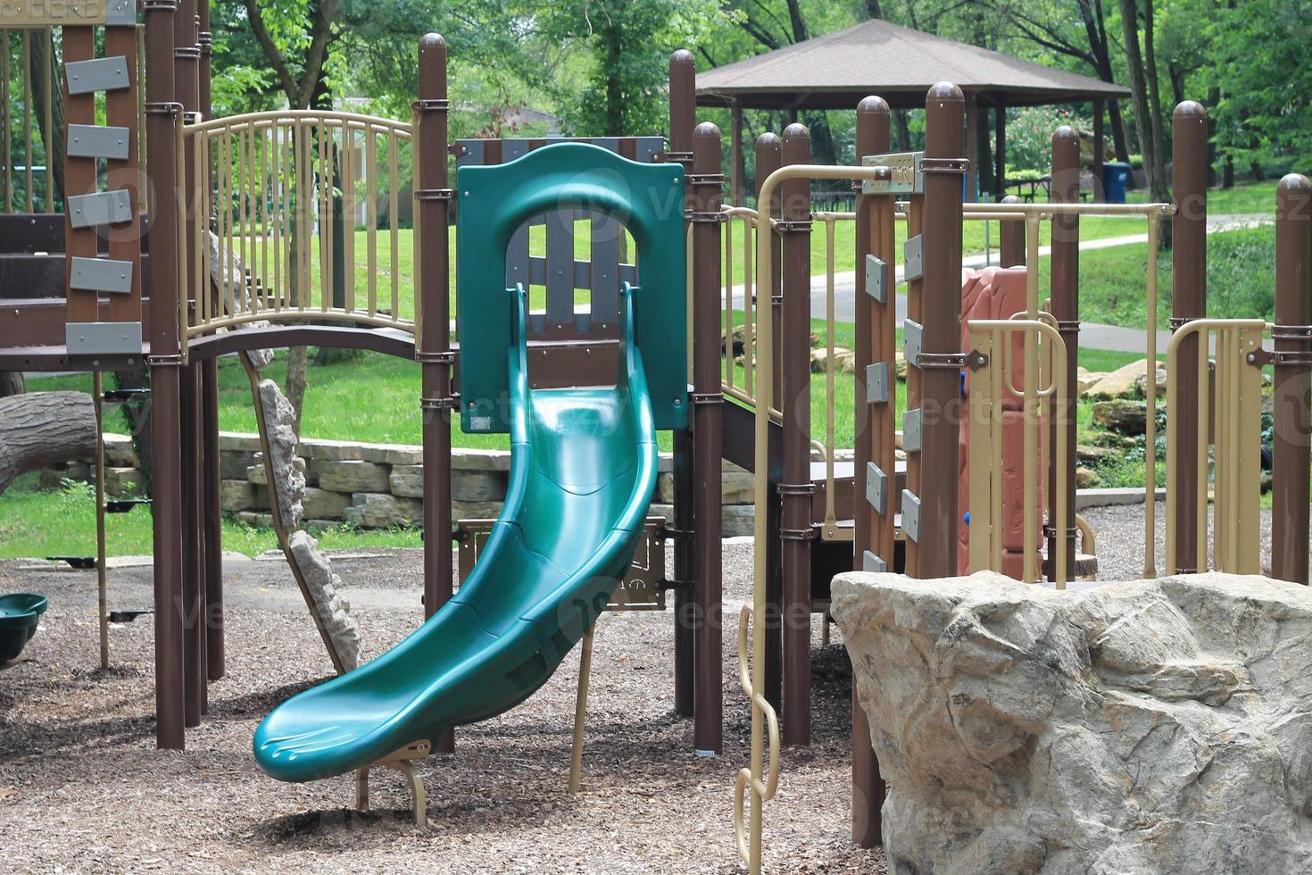 playground infantil com cobertura morta e escorregador verde foto