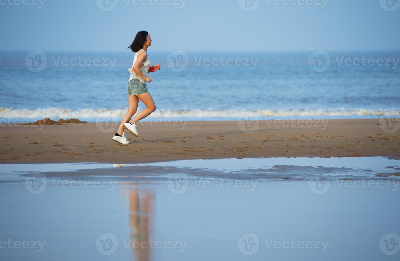 Woman running on beach at sunset. photo