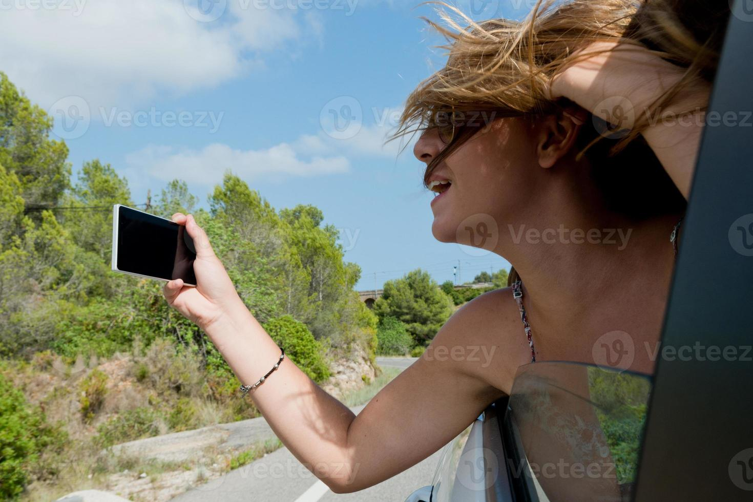 young woman takes a photo from his car