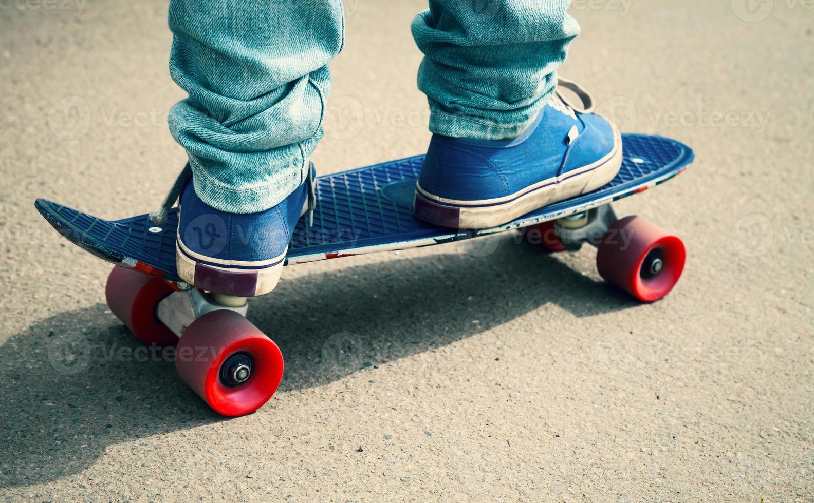 Skater en gumshoes de pie sobre su patín foto