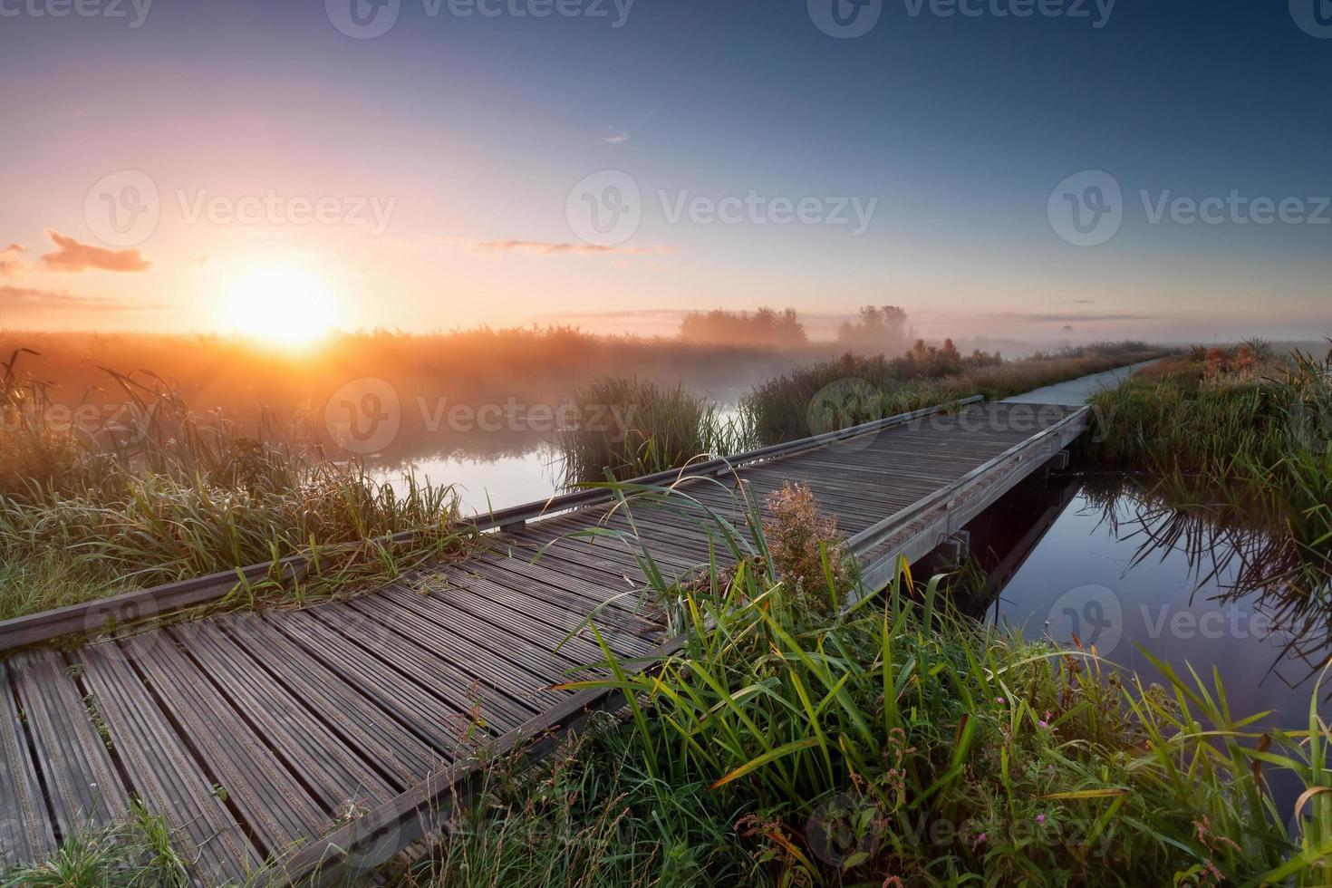nascer do sol enevoado sobre o caminho de madeira no lago foto