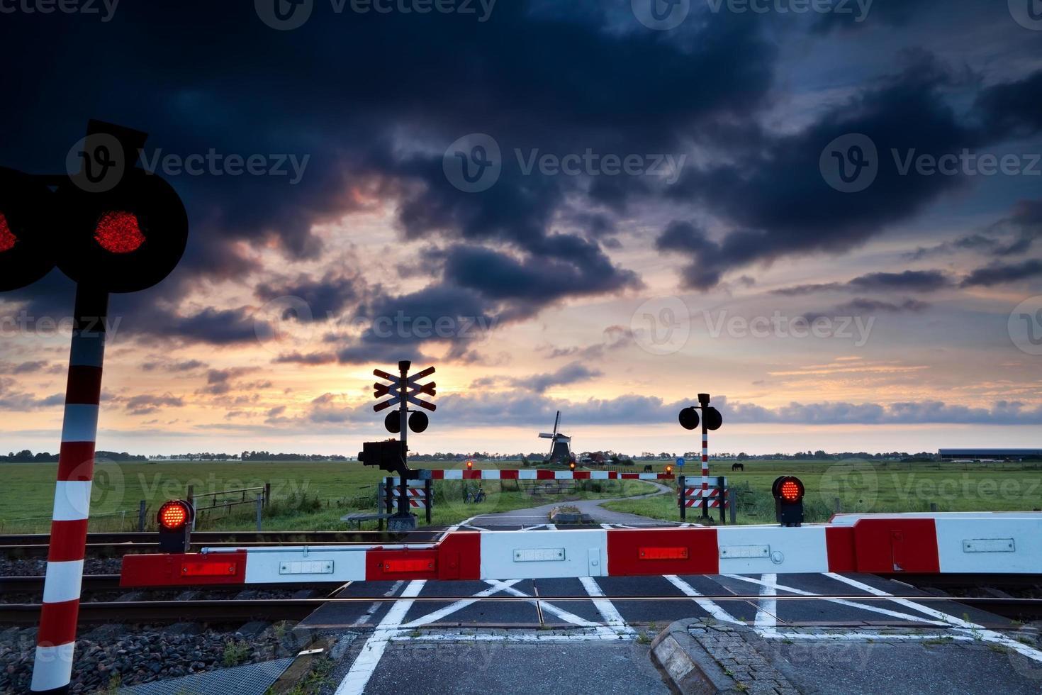 Cruce ferroviario cerrado al amanecer y molino de viento foto