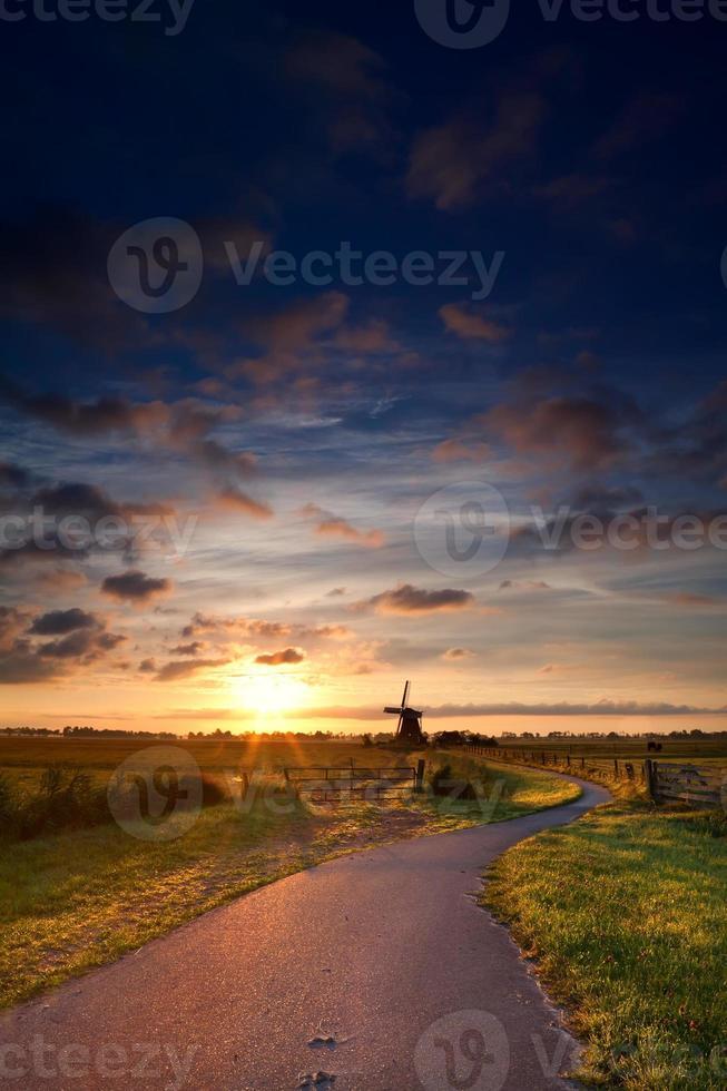 cálido amanecer de verano y molino de viento foto