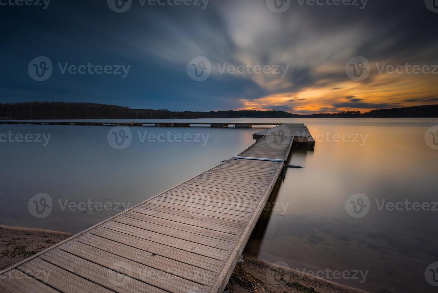 belo lago de longa exposição com cais ao pôr do sol. foto