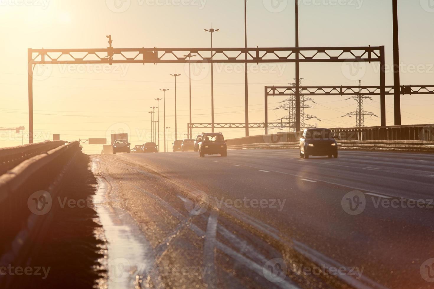 circular da cidade ao pôr do sol com silhuetas de veículos em movimento foto