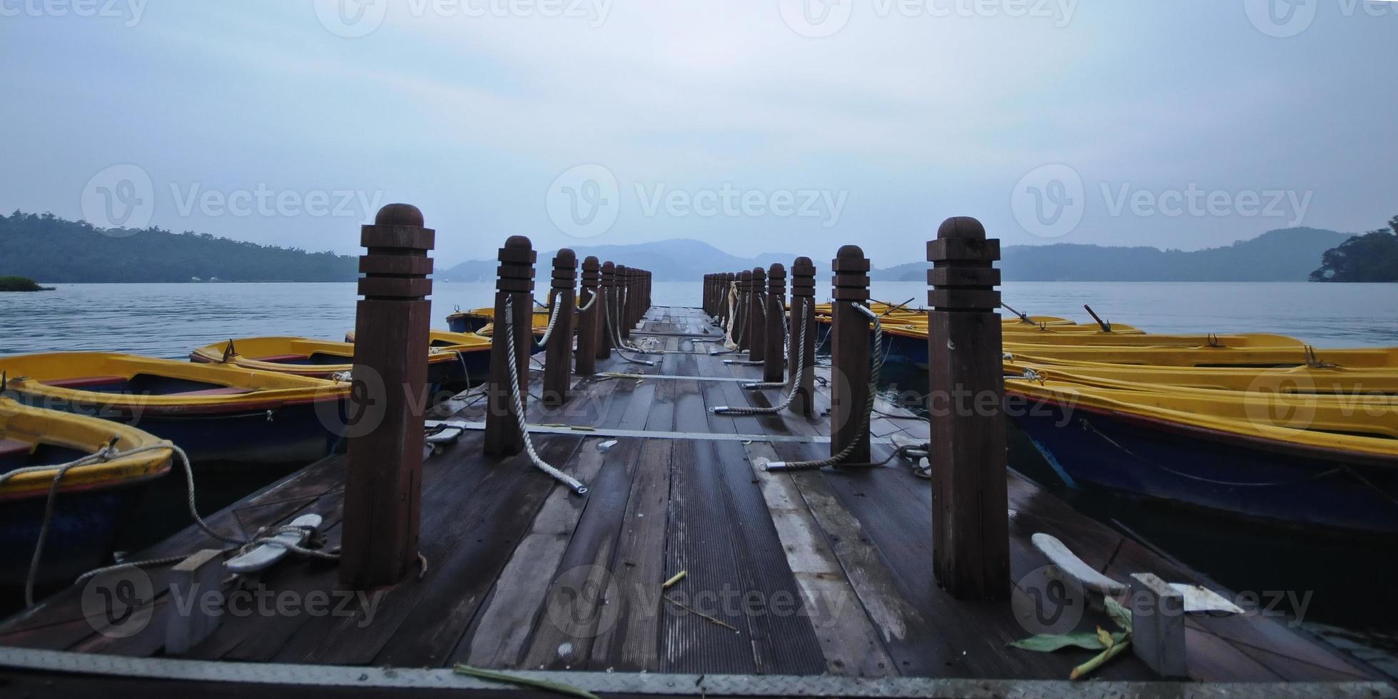 barcos a remo e cais de madeira pela manhã foto
