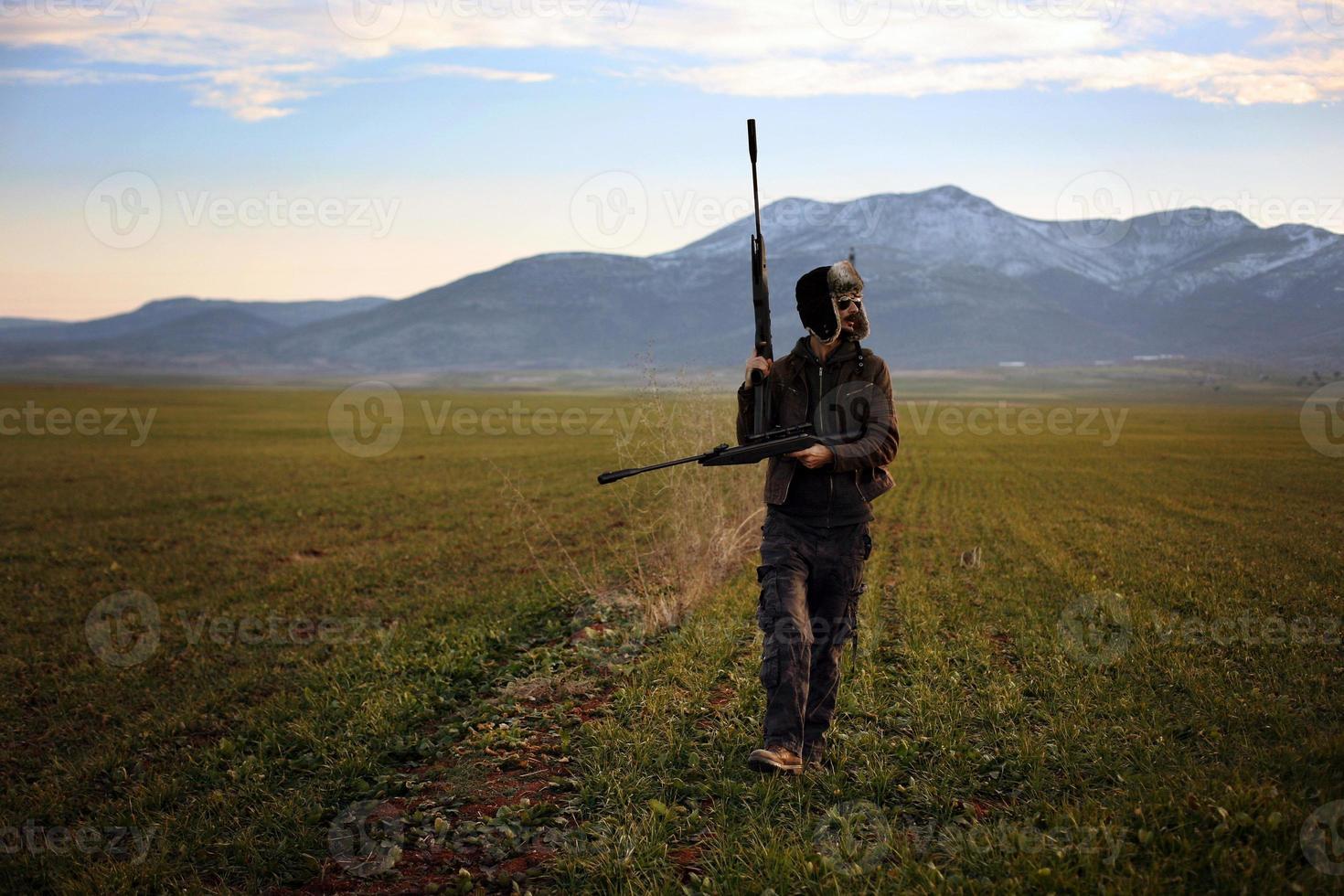 caçador mirar com um rifle foto
