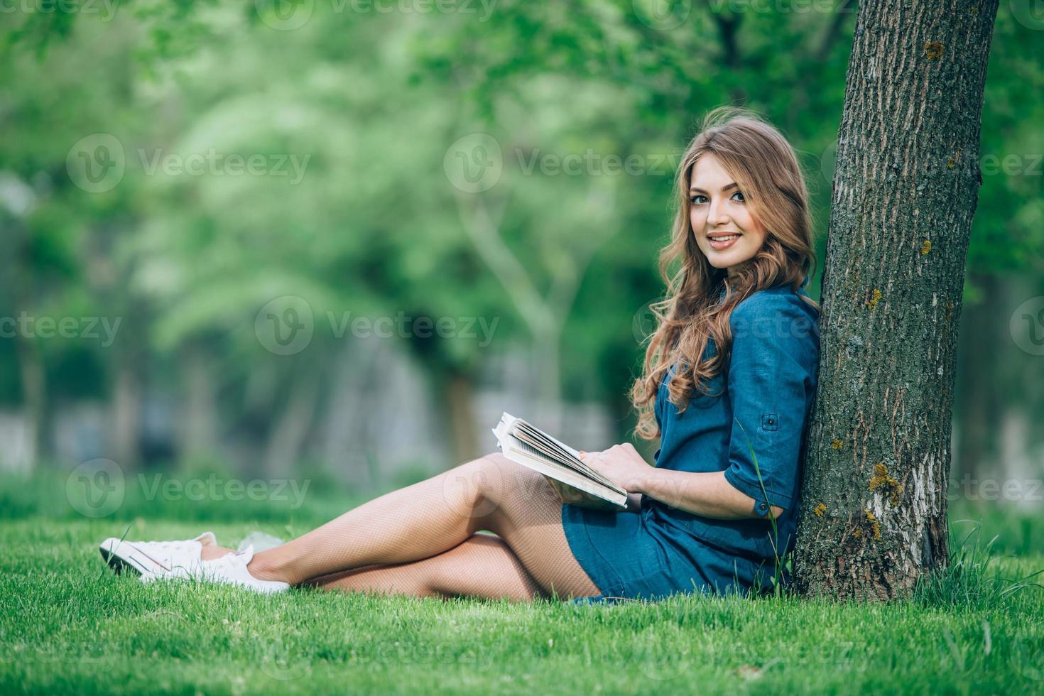 menina lendo um livro no parque foto