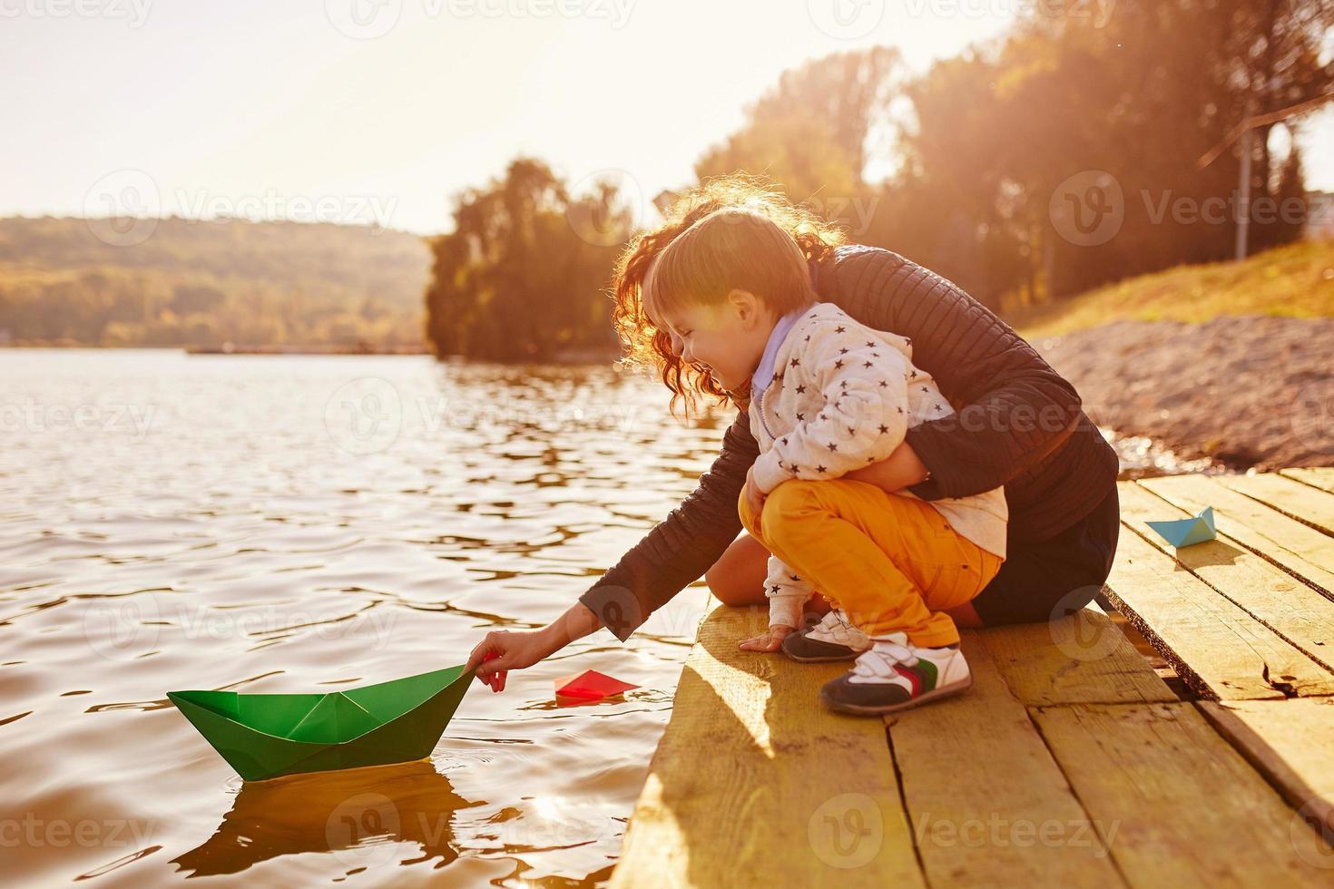 madre e hijo jugando con barcos de papel junto al lago foto