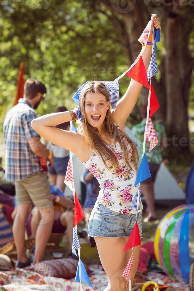 Pretty hipster posing for camera with flags photo