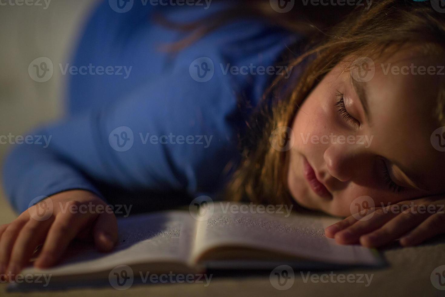 niña leyendo un libro en la lámpara de iluminación foto