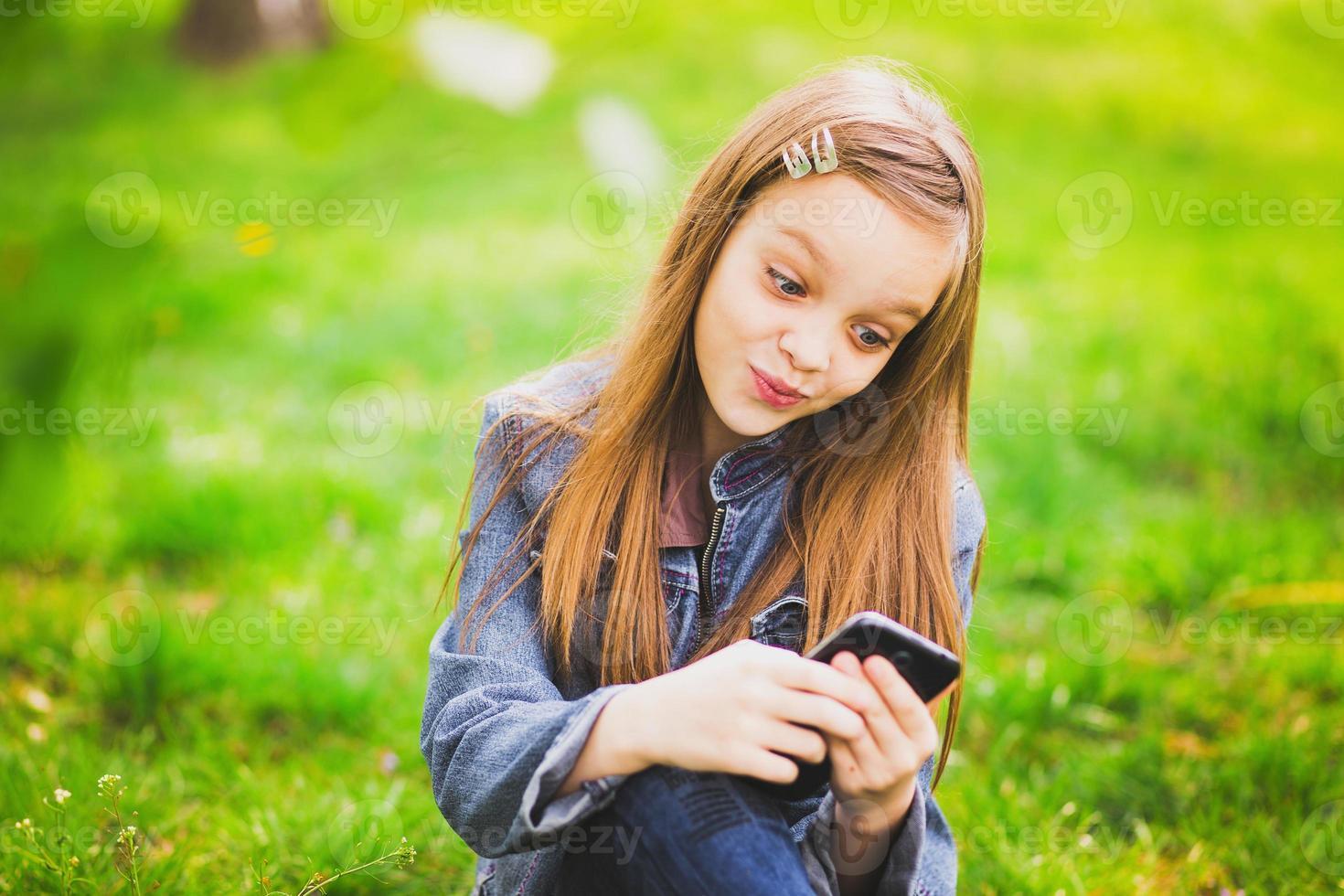 retrato, de, sonriente, adolescente, con, teléfono móvil foto