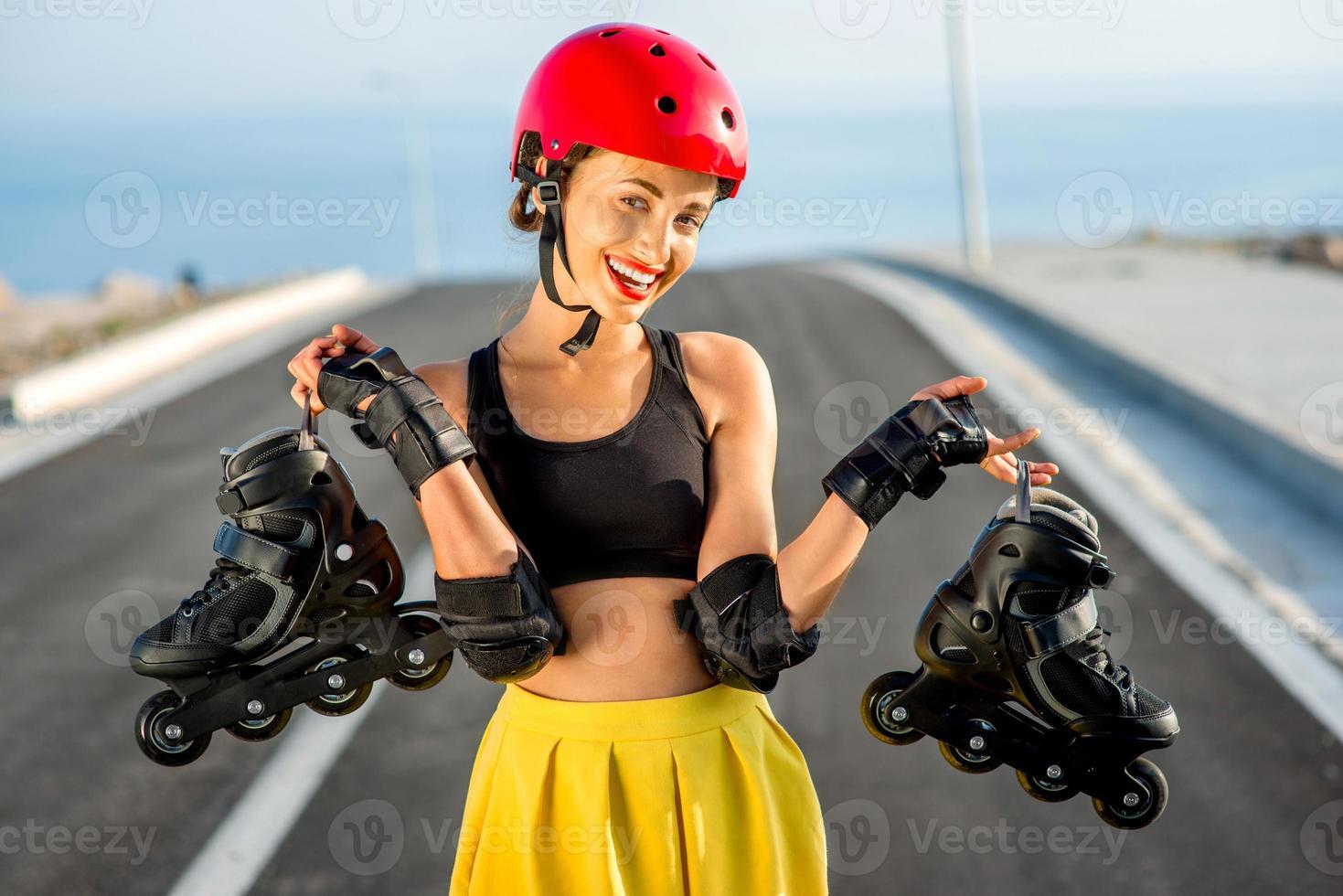 mujer deportiva con rodillos en la carretera foto