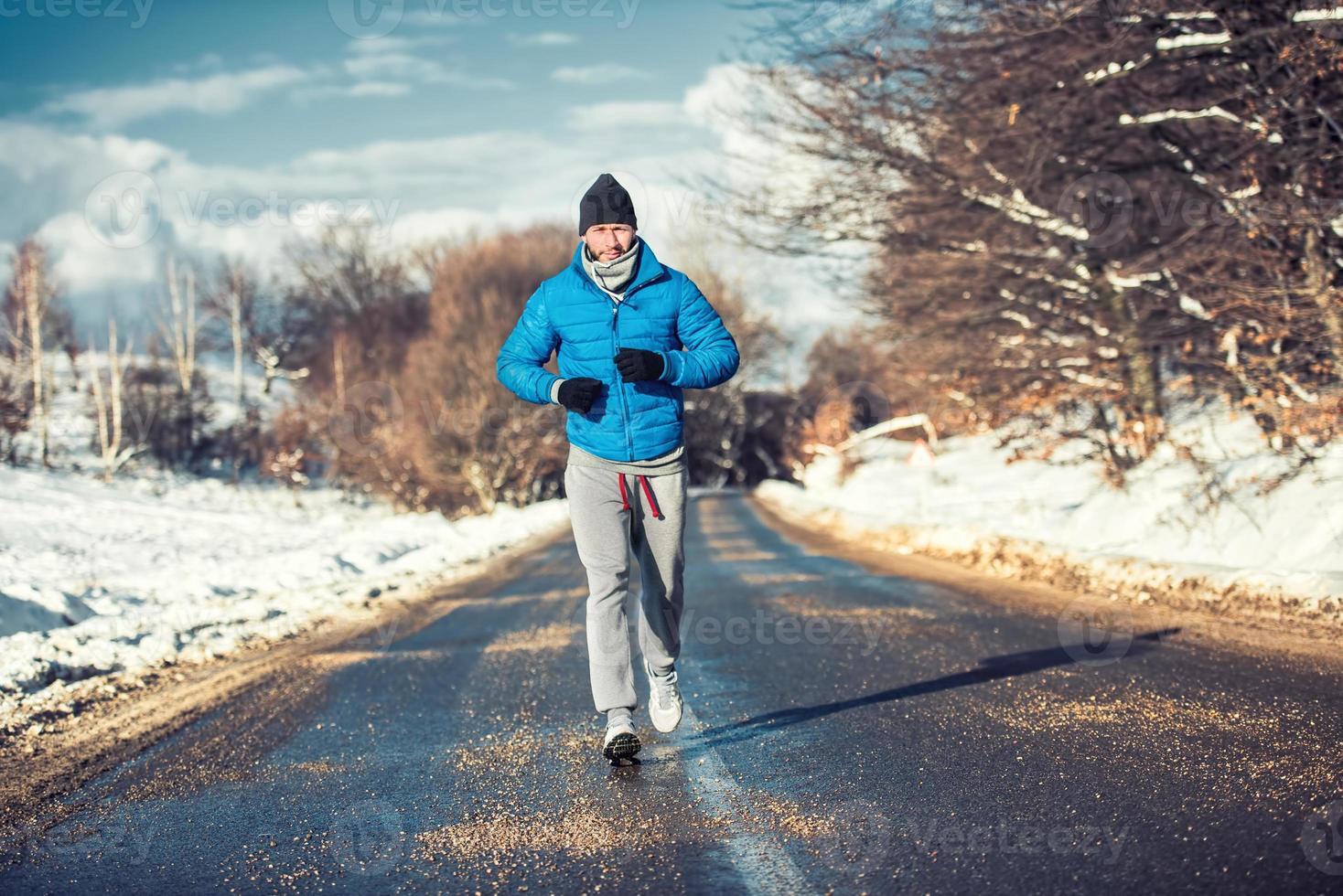 Hombre atleta musculoso trotar al aire libre en la nieve, entrenamiento para la práctica foto