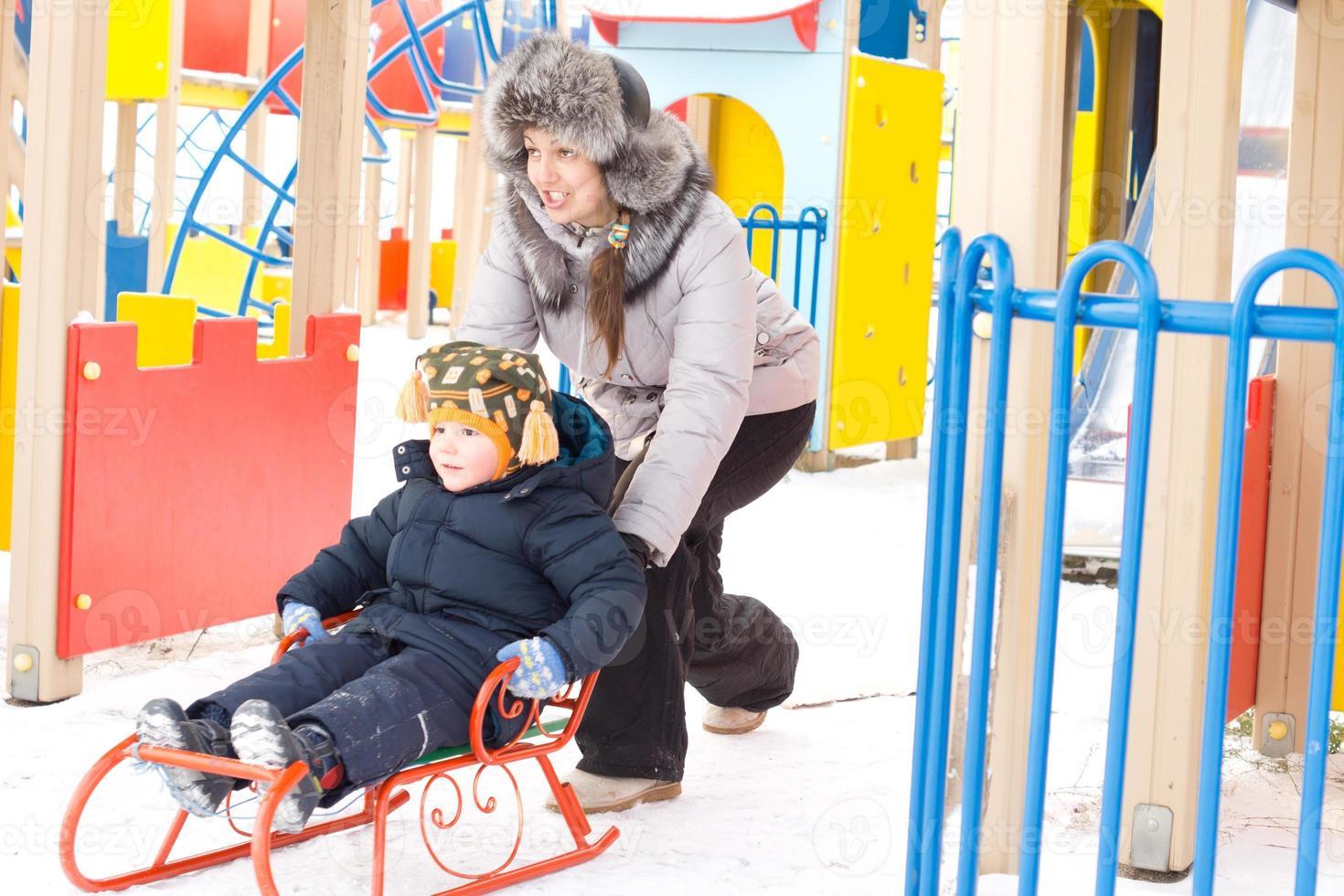 madre empujando a su hijo en un trineo de invierno foto