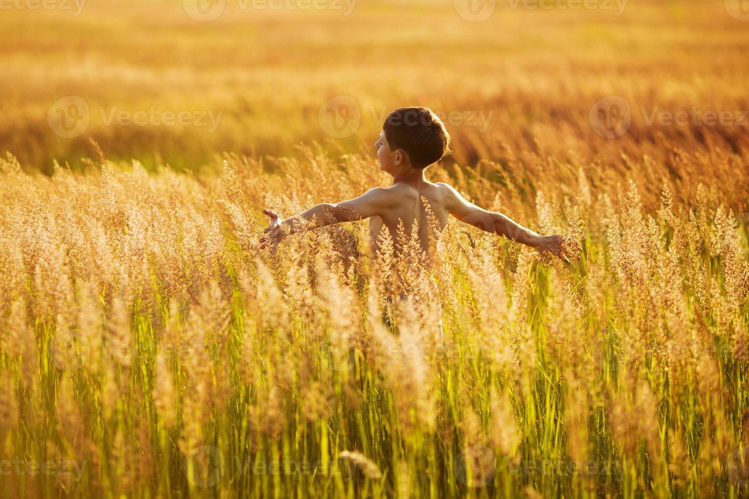 niño feliz corriendo en la hierba en una noche de verano foto