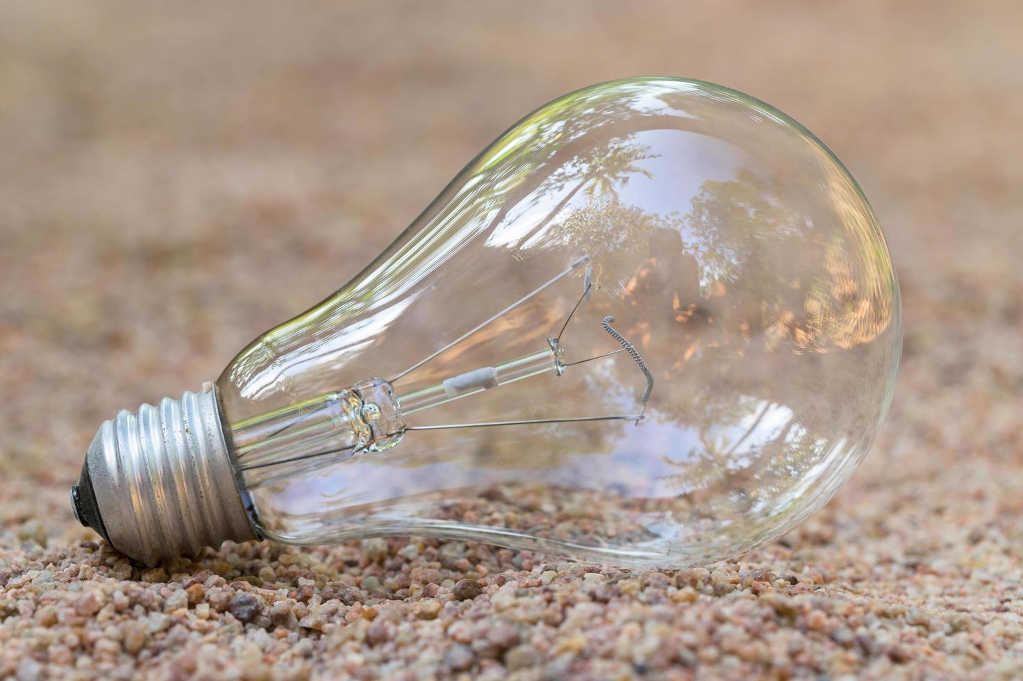 bombilla de luz en la arena foto