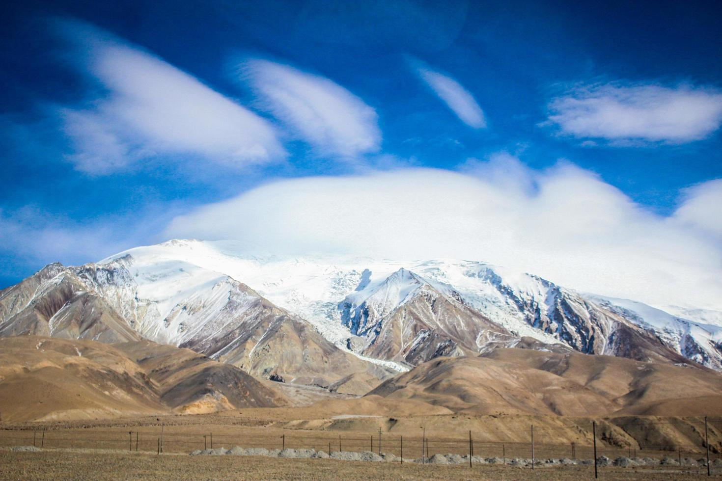 Snow-capped mountains under bright blue clouds photo