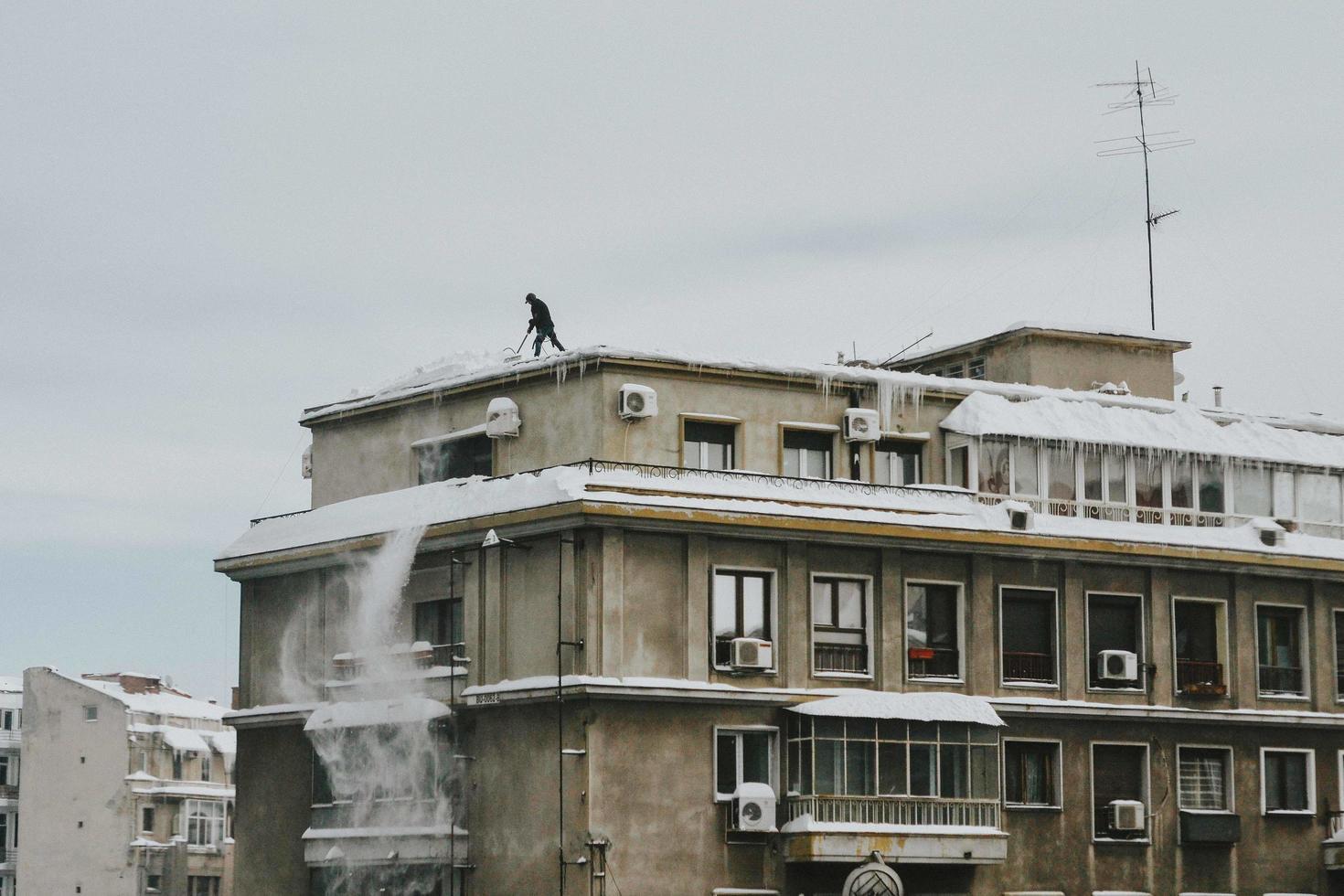 Bucarest, Rumania, 2020 - hombre empujando la nieve del techo foto