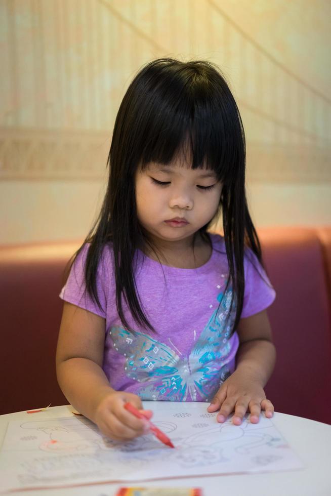 niña asiática sentada y coloreando una imagen en preescolar foto