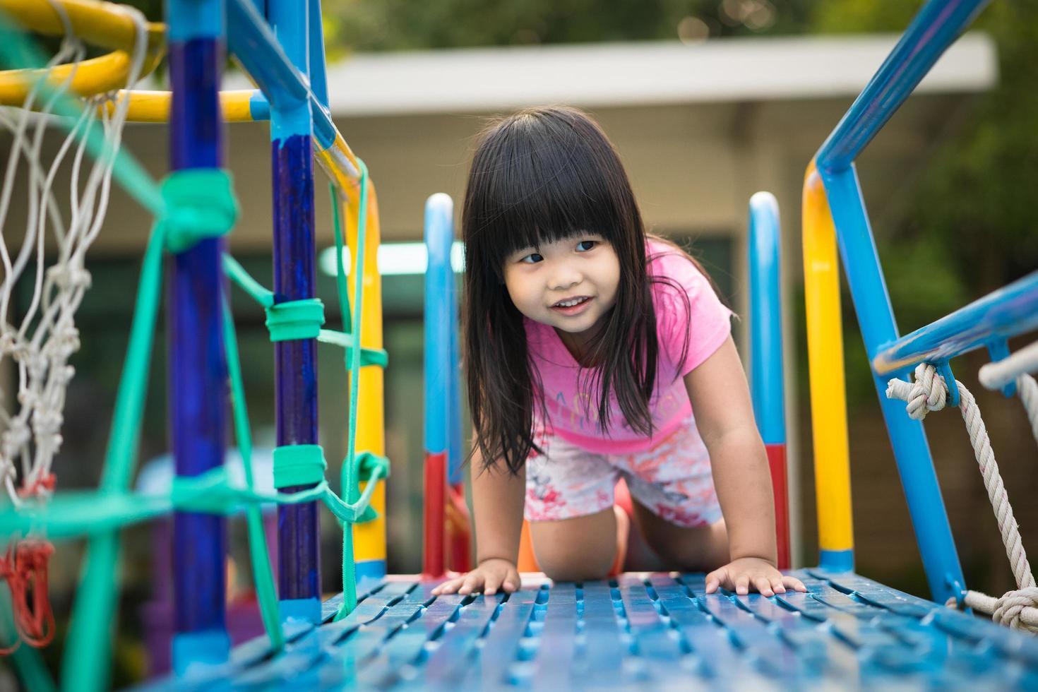 niña asiática disfruta jugando en el patio de recreo foto
