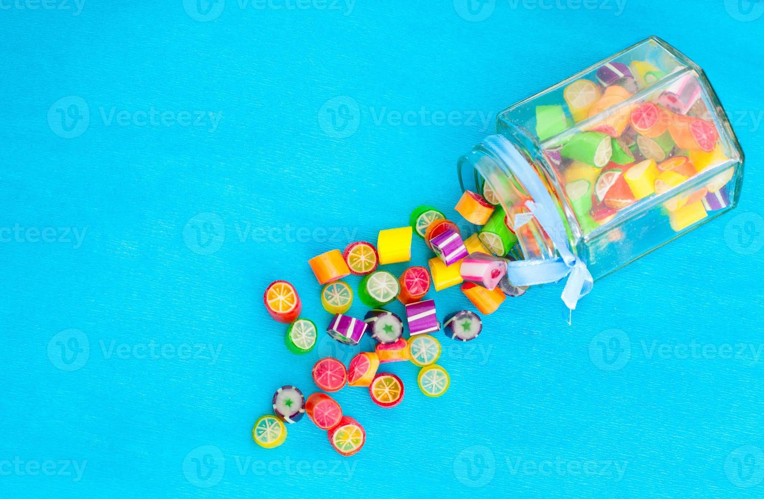 Colorful candies in jar on table on blue background photo