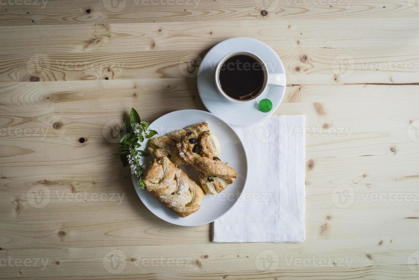 Breakfast with tea pastries and white flowers on wooden table photo