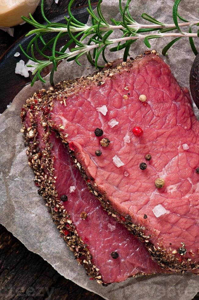 Raw beef steak with spices and a sprig of rosemary photo