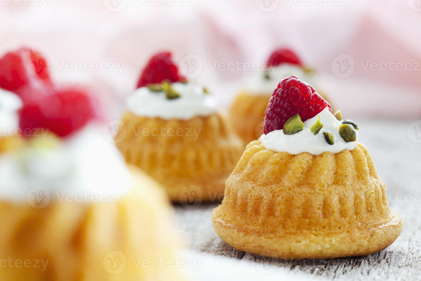Mini ring cakes with ricotta cream and raspberry on wood photo