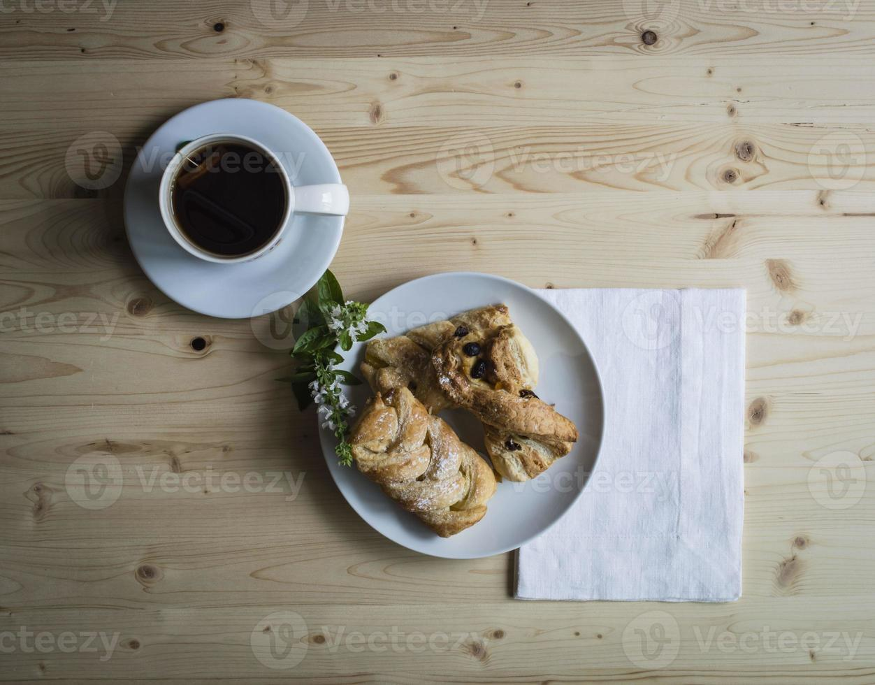 Breakfast with tea and pastries with little flowers on wooden table photo