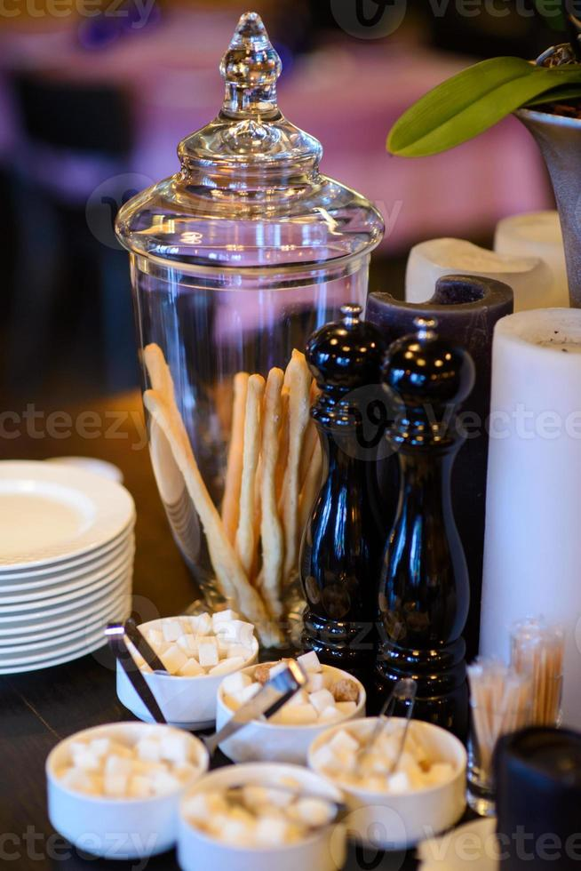 Glass vase with bread snack and decorative candles on table. photo