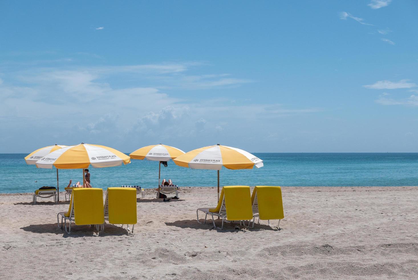 Miami, Florida, 2020 - Beachgoers with yellow umbrella and chairs on beach photo