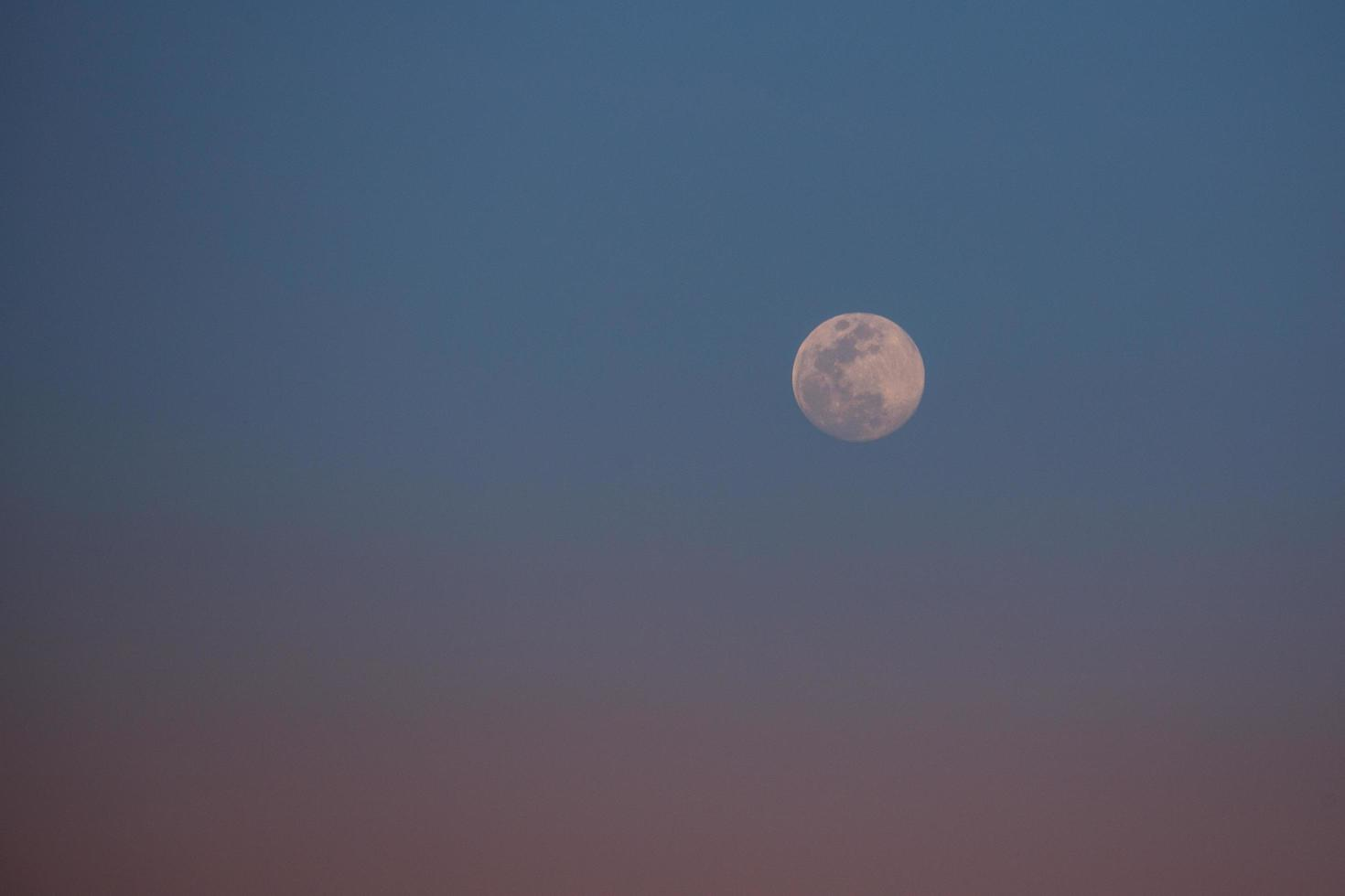 Pastel sunset with moon in sky photo