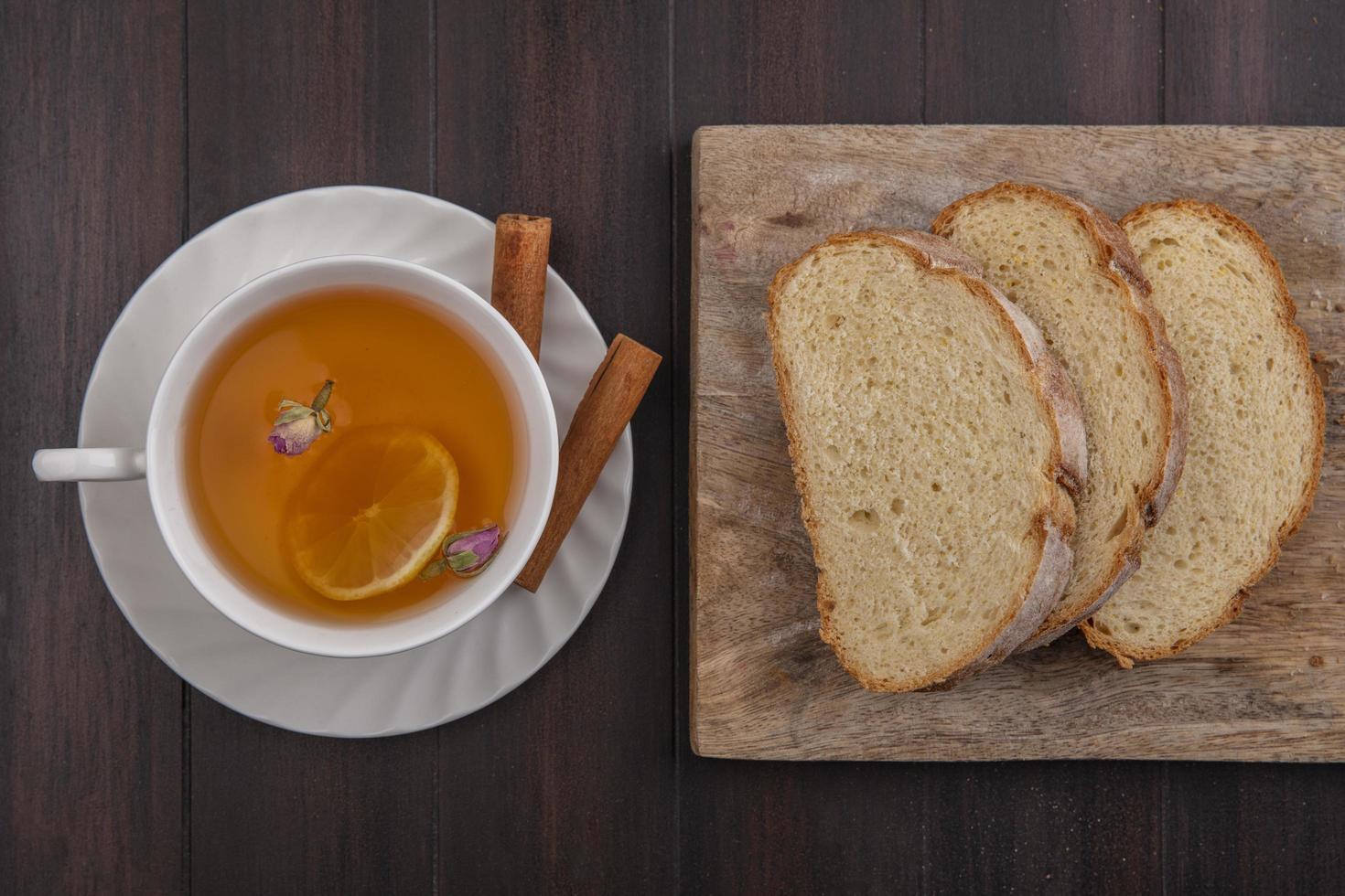 Fotografía de alimentos laicos plana de una taza de té con pan sobre fondo de madera foto