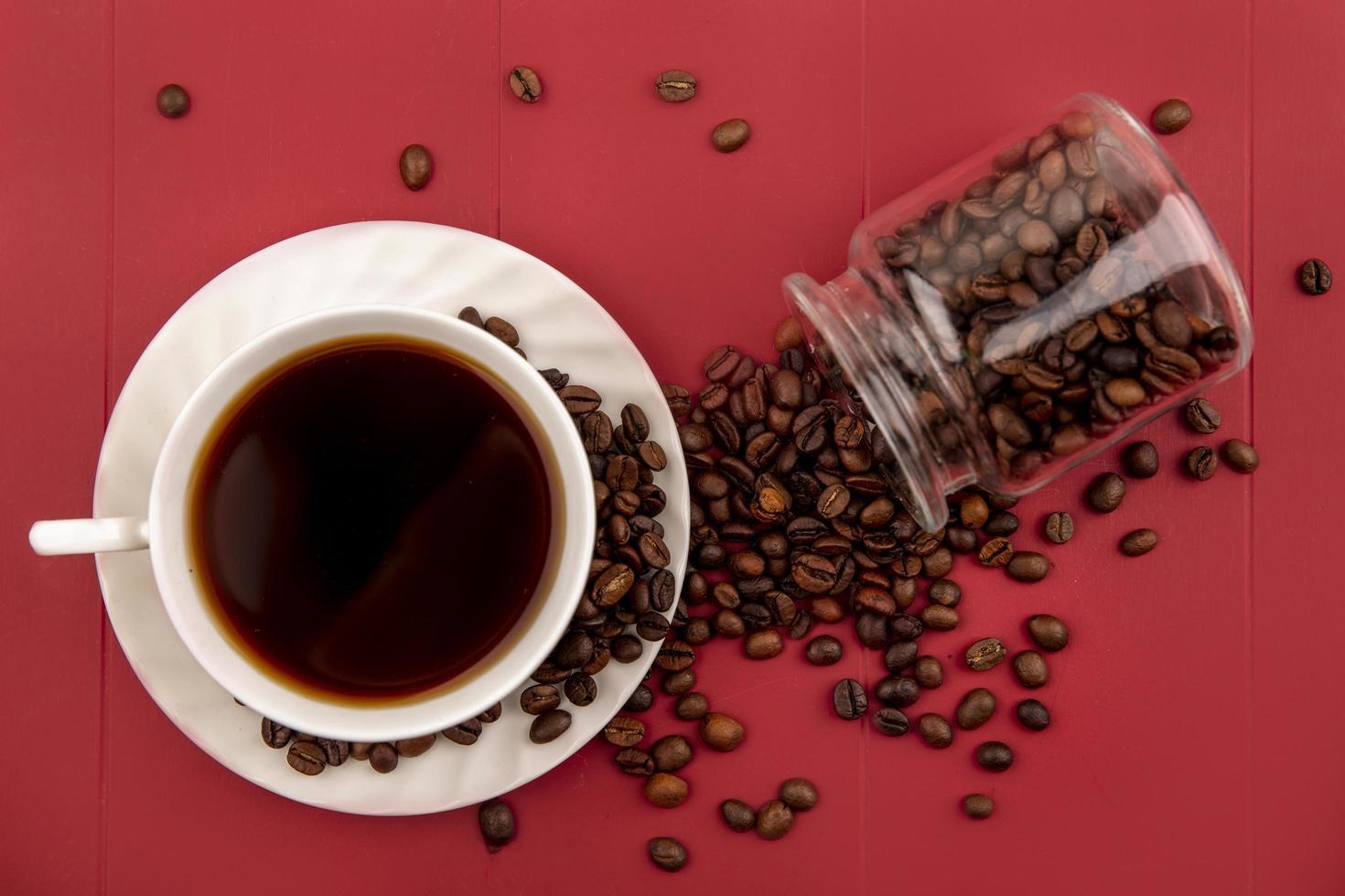 Fotografía de alimentos laicos plana de una taza de café y granos de café sobre fondo rojo. foto
