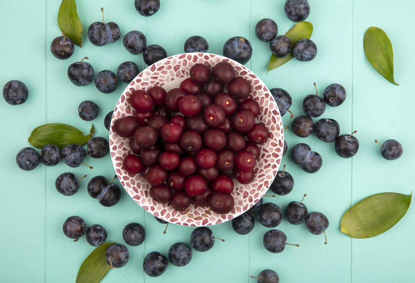 Fotografía de alimentos laicos plana de deliciosas cerezas rojas sobre fondo azul. foto